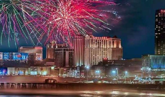 fireworks going off over the boardwalk in atlantic city with casinos in the background