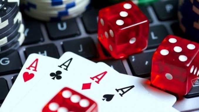 dice, cards, and poker chips on a laptop keyboard