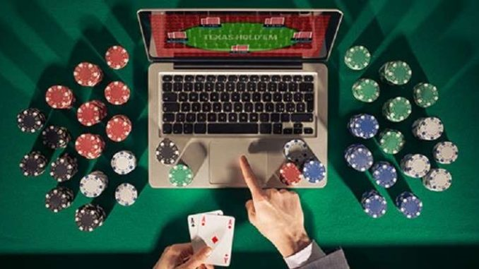 man playing online poker on a laptop computer with chips stacked around the table