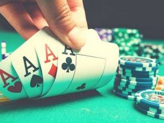 poker player showing four aces at table with poker chips