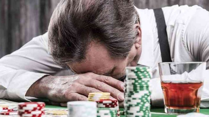 man with head in hands at poker table