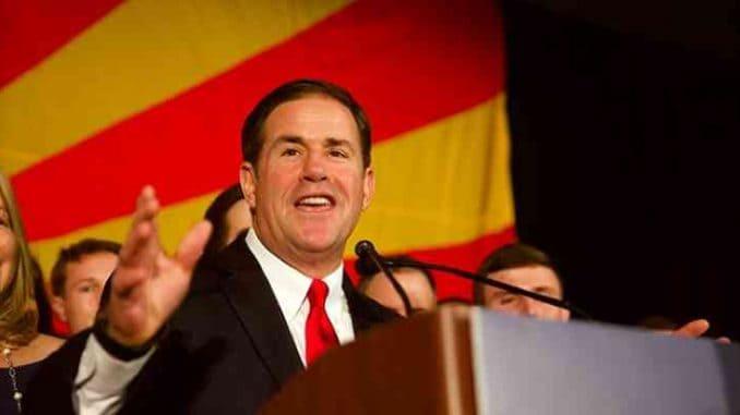 az governor doug ducey smiling at podium