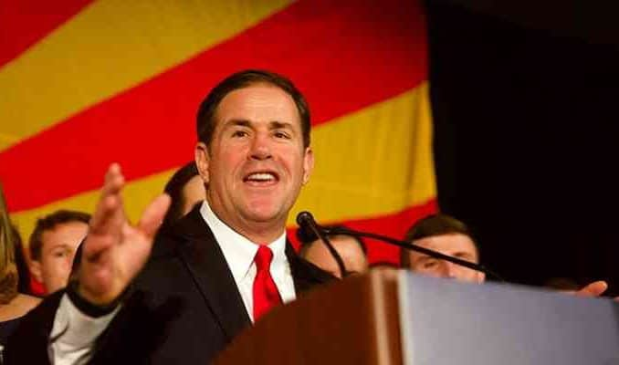 az governor doug ducey smiling at podium